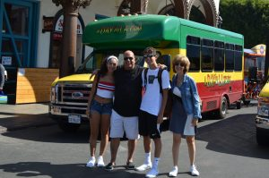 Family poses in front of the A Day in LA Tours bus. A Day in LA Tours is considered one of the best tours in Los Angeles.