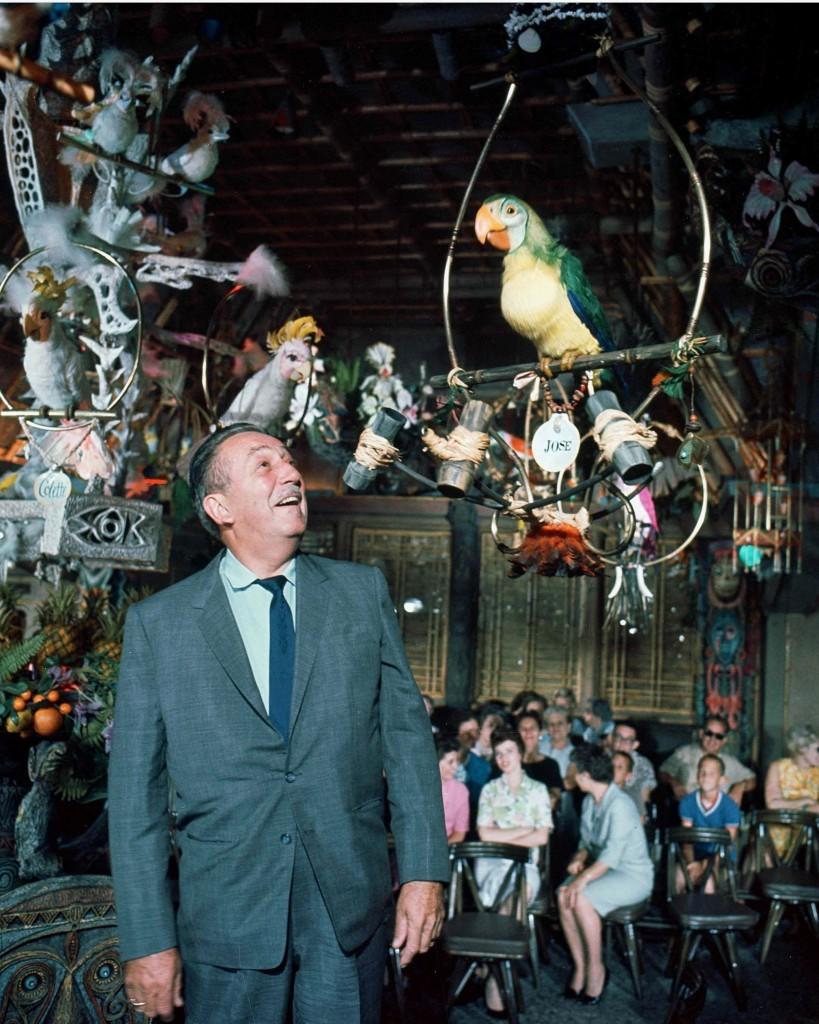 Walt Disney looks up at a mechanic parrot