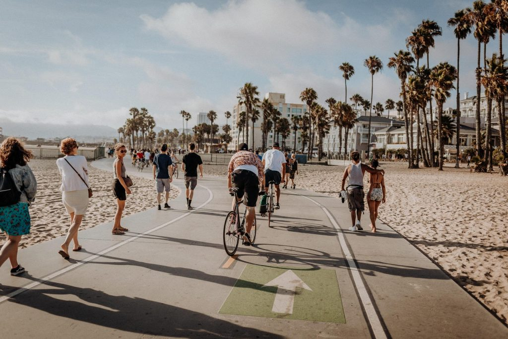 Bicyclist bike down a sidewalk near venice beach